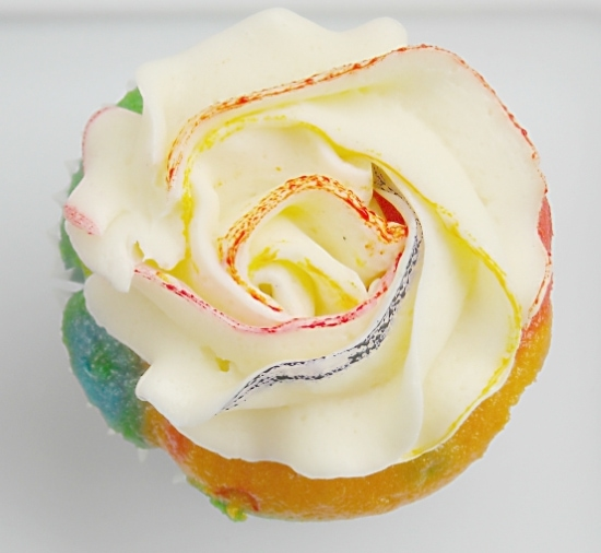 A rainbow cupcake with rosette frosting